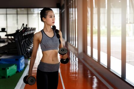 Fitness woman doing workout biceps with dumbbells at gym. Healthy lifestyle concept.