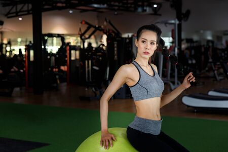 Fitness woman sitting on a fitness ball at gym. Healthy lifestyle concept. Reklamní fotografie