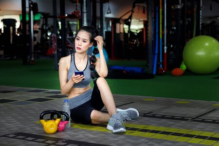 Active woman sitting on the floor and using smartphone while resting after hard workout in fitness gym. Reklamní fotografie