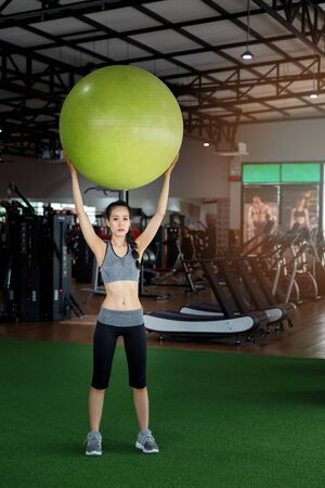 Fitness woman doing exercises with a fitness ball at gym. Healthy lifestyle concept.