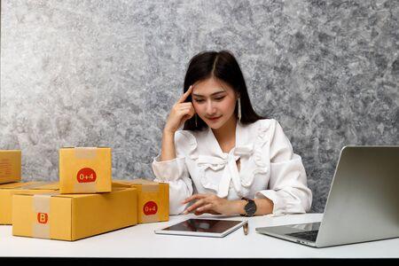 Odnosząca sukcesy przedsiębiorcza kobieta biznesu ze sprzedażą online i wysyłką paczek w swoim domowym biurze, przygotowuje paczkę z produktem do dostarczenia do klienta. Zdjęcie Seryjne