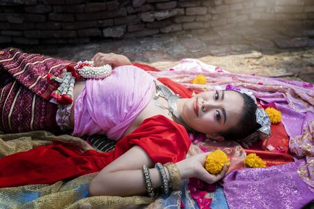 Beautiful Thai woman wearing thai traditional clothing lie down on silk of various colors.