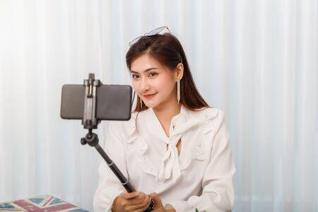 Beautiful Asian woman taking selfie by her smart phone. Banco de Imagens