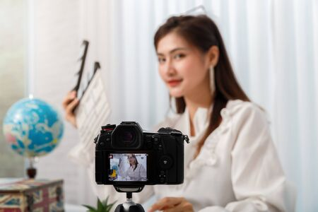 Young asian woman traveler blogger selfie herself with smart phone while recording vlog video live streaming.