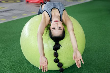 Fitness woman doing abs crunches on a fitness ball at gym. Healthy lifestyle concept. Reklamní fotografie