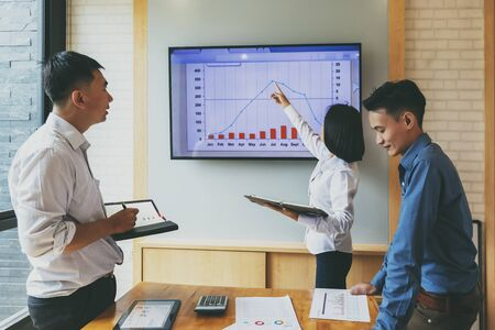Beautiful businesswoman gives report or presentation to her business colleagues in the conference room. She show graphic charts and companys growth on the wall TV. Reklamní fotografie
