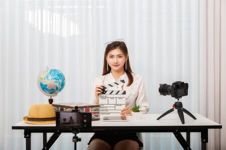 Young asian woman traveler blogger holding clapper board while recording vlog video live streaming. blogger and vlogger online influencer on social media concept. Reklamní fotografie