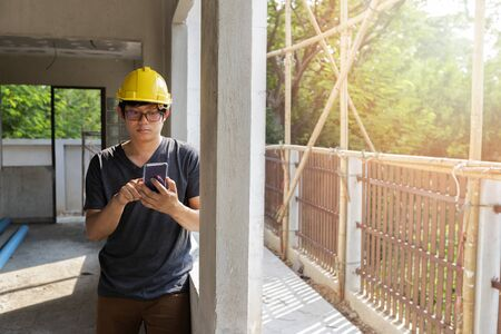 Engineer or Architect using cell phone in building construction site.