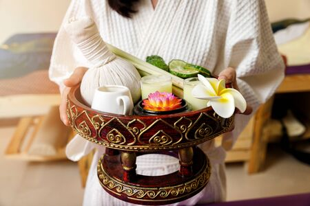 Woman holding basket of Kaffir lime or bergamot, lemongrass and other thai herbs in thai spa and massage shop.