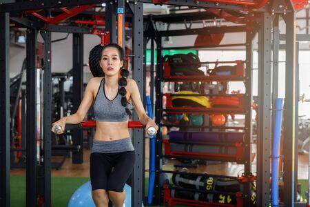 Fitness woman doing workout leg raises exercise at gym. Healthy lifestyle concept. Banco de Imagens