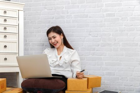Successful entrepreneur business woman accepts orders from customer via online sales in her home office, prepare parcel box of product for deliver to customer. Reklamní fotografie