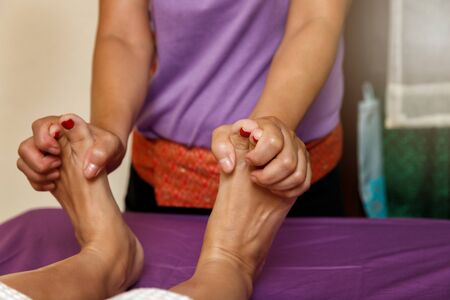 Woman receiving foot massage service from masseuse in spa salon thai spa and massage shop. Reklamní fotografie