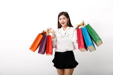 Portrait of an excited beautiful woman holding shopping bags isolated on white.
