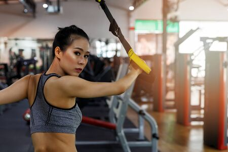 Fitness woman training with fitness straps in gym. Healthy lifestyle concept.