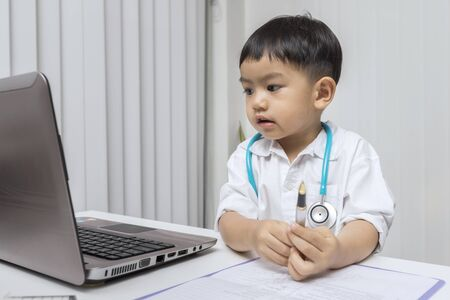 Little boy in medic uniform holding a pen on desk. Childhood dream and Careers in children's dreams concept. 写真素材 - 129910821