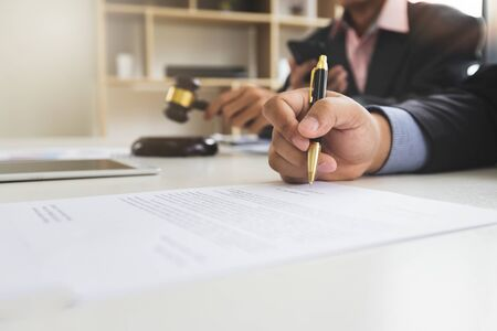 Businessman is signing a business contract with a lawyer or legal counsel sitting next to him. Commercial law and Business cooperation concept.