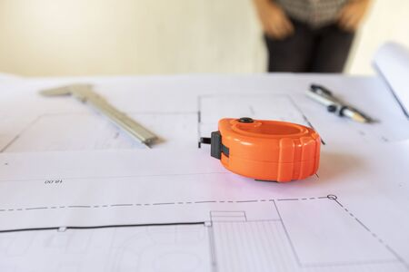 A measuring tape on house blueprint plan.