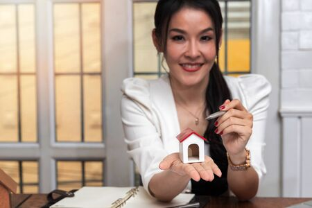 Business, architecture, building construction and real estate concept. Female real estate agent presenting a house model. Young female architect holding model of house in office.