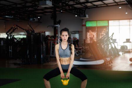 Donna fitness facendo allenamento sumo squat con kettlebell in palestra. Concetto di stile di vita sano.