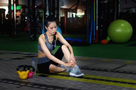 Sport woman injured at ankle in fitness training gym. Healthy lifestyle concept. Reklamní fotografie