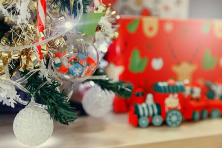Decorated Christmas tree lights twinkling and sparkling and Christmas wooden train toys with snowman and friends and gift box in background. Фото со стока