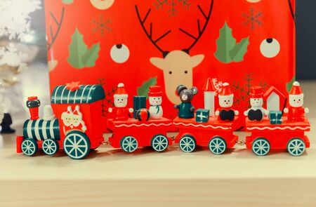 Christmas wooden train toys with snowman and friends and gift box in background. Фото со стока - 129916260