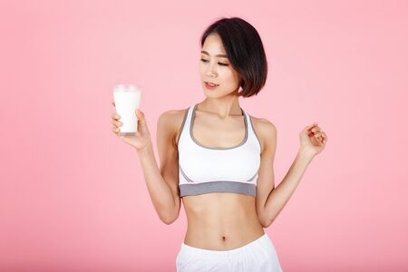 Beautiful young healthy woman hold a glass of milk isolated pink background. Fitness Diet and healthy eating concept.