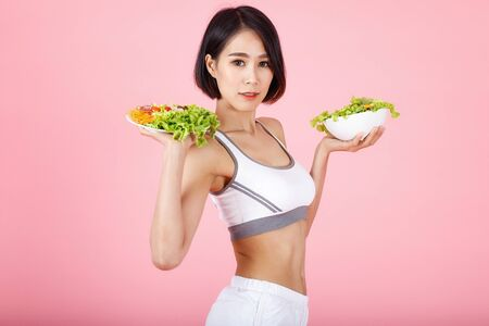 Beautiful young healthy woman with salad bowl isolated over pink background. Fitness Diet and healthy eating concept.