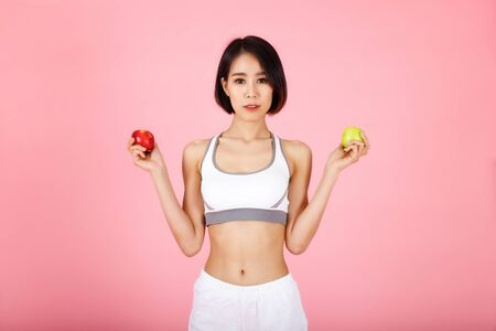 Beautiful young healthy woman with red apple and green apple isolated over pink background. Diet and healthy eating.