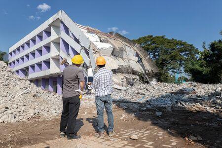 Supervisore e appaltatore del controllo di demolizione che discutono sulla demolizione dell'edificio.