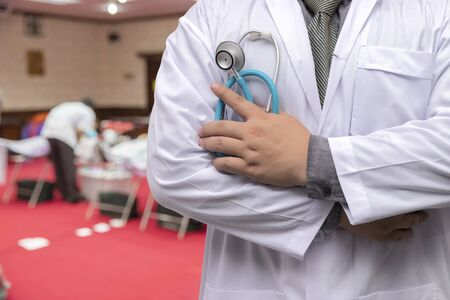 Doctor in gown uniform with stethoscope standing and fold his arms over the chest in blood donor room
