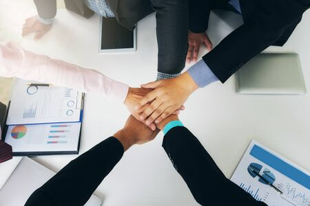 Concept of teamwork: Top view of hands of business team showing unity with putting their hands together.