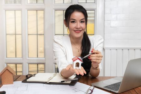 A house model on hand of Female real estate agent. Young female architect holding model of house in office. Business, architecture, building construction and real estate concept.