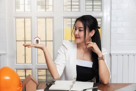 Business, architecture, building construction and real estate concept. Female real estate agent presenting a house model.