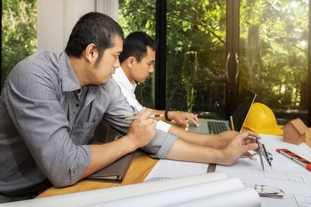 Confident team of architect working together in a office.They discussing about new startup project on desk. Architect discuss with engineer about project in office, architectural concept