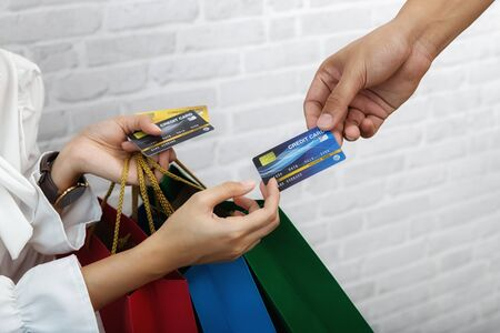 Salesman holding a credit card swipe machine or electronic data capture along with accepting credit cards from customers. Customer using credit card for payment.
