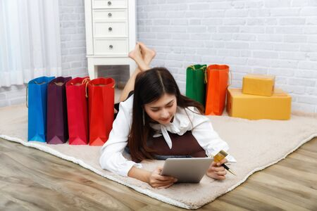 Asian woman using laptop to shopping online while lying on carpet at her home. Technology e-commerce and shopping online concept.