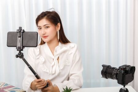 Young asian woman blogger selfie herself with smartphone while recording vlog video live streaming. blogger and vlogger online influencer on social media concept.