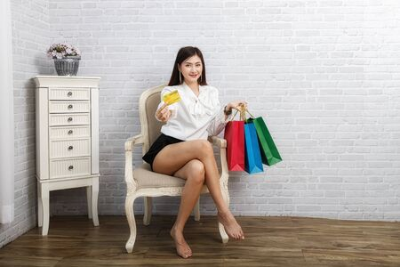 Credit card in beautiful woman hand and holding shopping bags while sit on vintage chair.