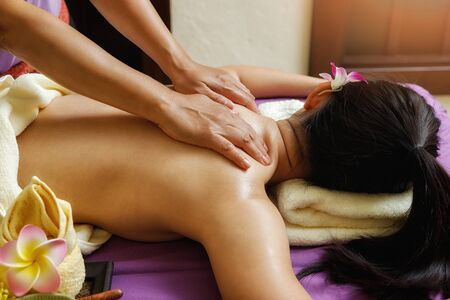 Asian woman enjoying back massage in massage salon. Beauty treatment concept. Фото со стока