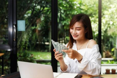 Beautiful young woman counting us dollar money. business, finance, saving, banking and online shopping concept.