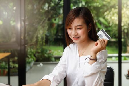 Smiling beautiful Asian woman presenting credit card in hand showing trust and confidence for making payment. Online shopping concept.