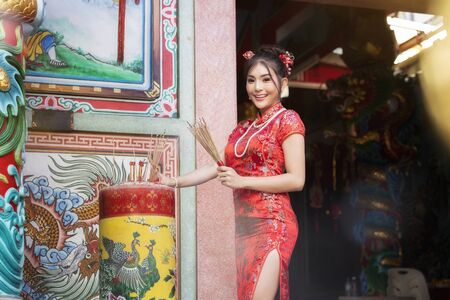 Concept to celebrate Chinese New Year, Vegetarian Festival : Chinese woman in a red cheongsam dress holding incense pay homage to Chinese god at shrine. Stock Photo