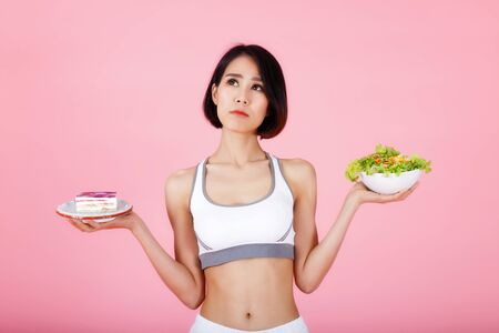 Young woman choosing between piece of cake and healthy salad isolated on pink background. Healthy eating, diet, nutrition, weight loss concept. Stock Photo