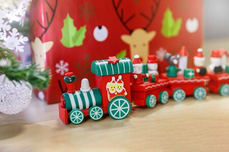 Christmas wooden train toys with snowman and friends and gift box in background.