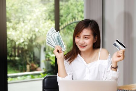 Beautiful young woman holding us dollar money and credit card. business, finance, saving, banking and online shopping concept. Фото со стока