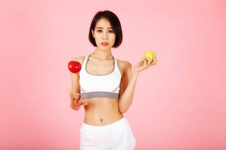 Young slim fitness asian woman in white sportswear throwing up a red apple isolated on pink background.