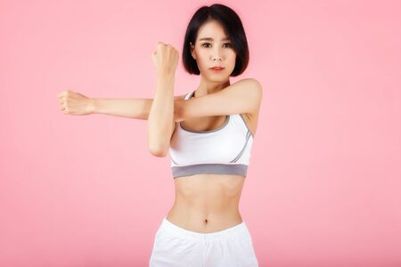 Young sporty woman doing shoulder and arm stretching isolated on pink background. Фото со стока