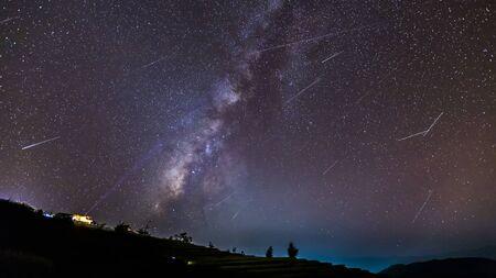 Paisaje nocturno de larga exposición con la vía láctea durante la lluvia de meteoritos sobre una montaña con cabaña.
