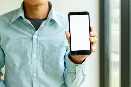 Homme tenant un smartphone à la main. Homme d'affaires montrant un smartphone. Banque d'images